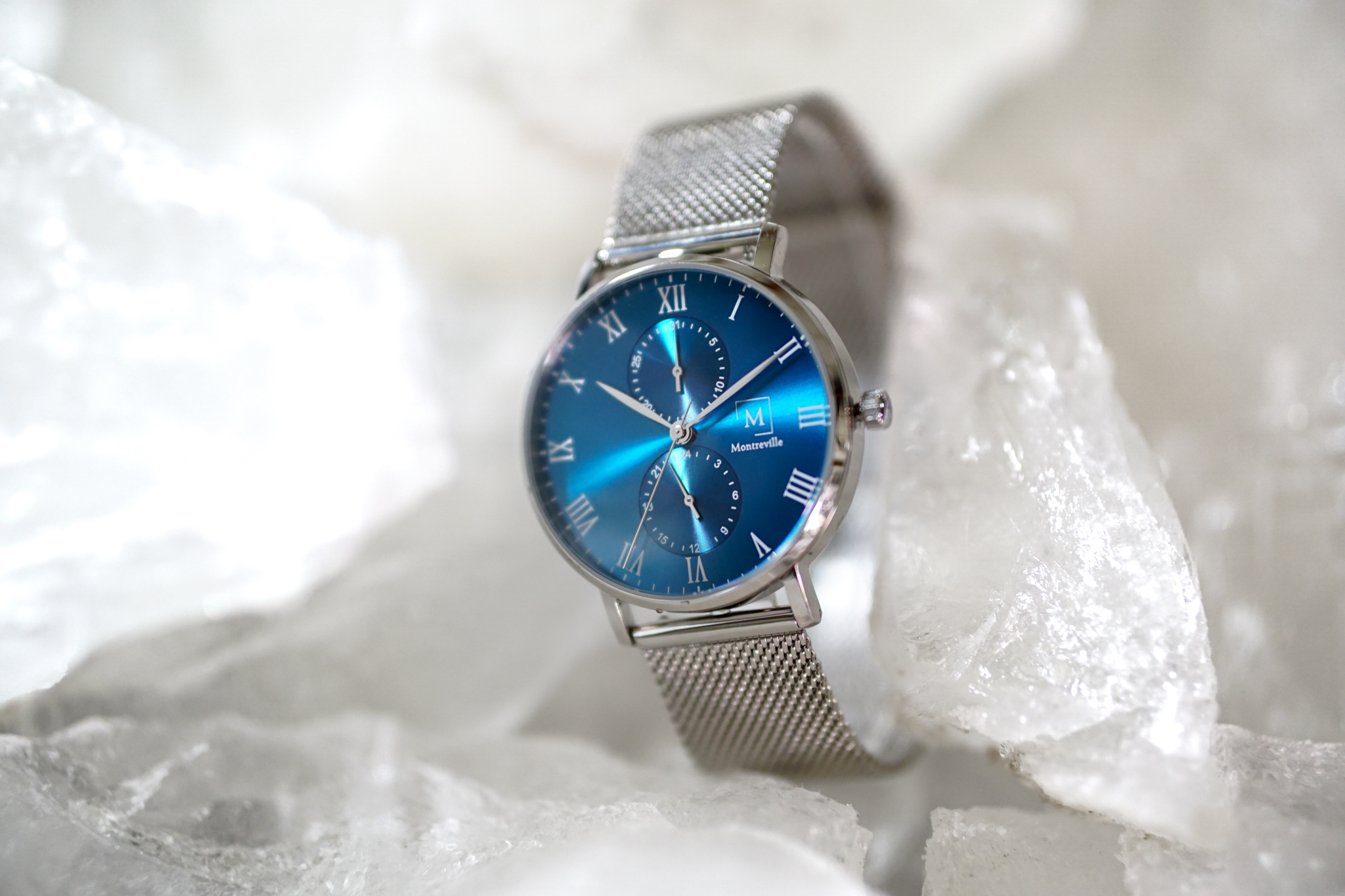 a silver watch laying on ice cubes