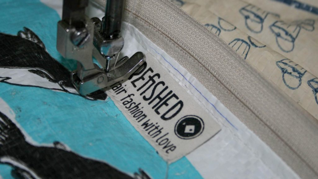 A sewing machine sewing a Refished label on the inside of a bag