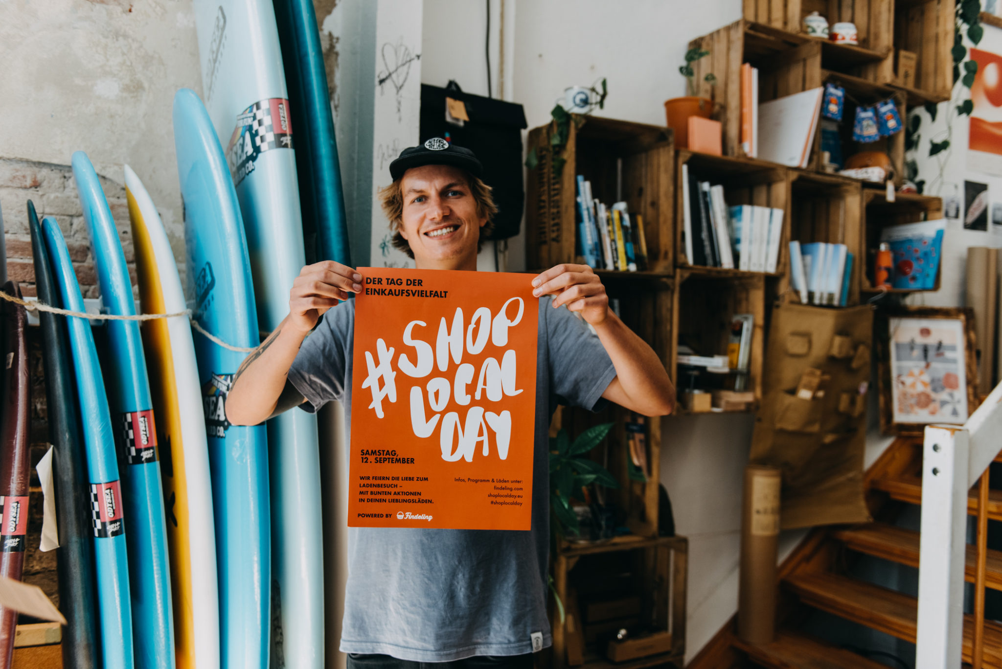 A store owner is showing the Shop Local Day poster